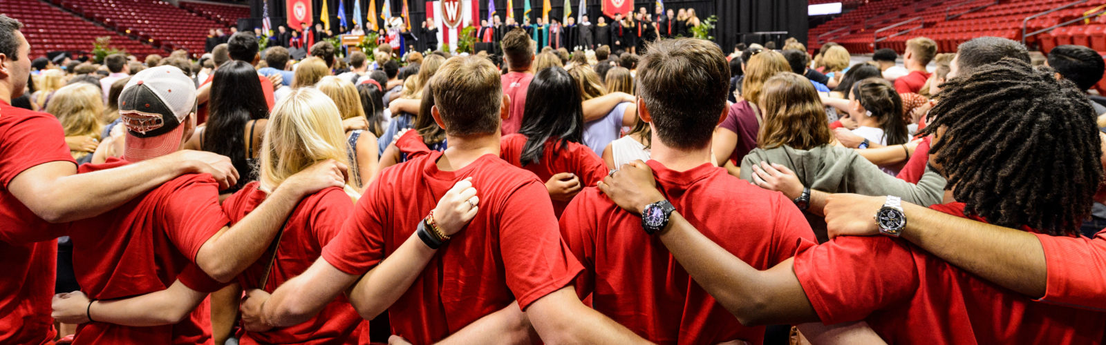 "First-year students link arms and sing ""Varsity"" at the end of the Chancellor's Convocation for New Students, a Wisconsin Welcome event held at the Kohl Center at the University of Wisconsin-Madison on Sept. 2, 2016. (Photo by Jeff Miller/UW-Madison)"