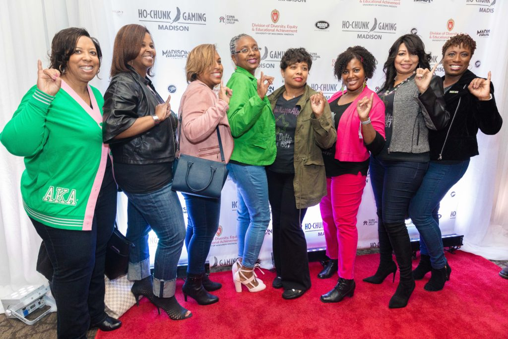 Eight alumni women pose holding up a hand symbol for their sorority, Alpha Kappa Alpha, on a red carpet in front of a backdrop with logos for Ho-Chunk Gaming, CUNA Mutual Group, Rough Sportswear and the DDEEA.