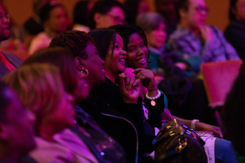 Members of the audience laugh while watching T. Murph perform.