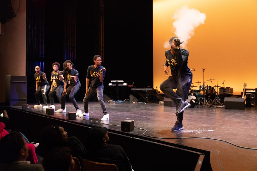 Five members of the Alpha Phi Alpha fraternity stand on stage during a step routine. Four members are looking at the fifth one, who is blowing a white powder into the air while posing standing on one leg.