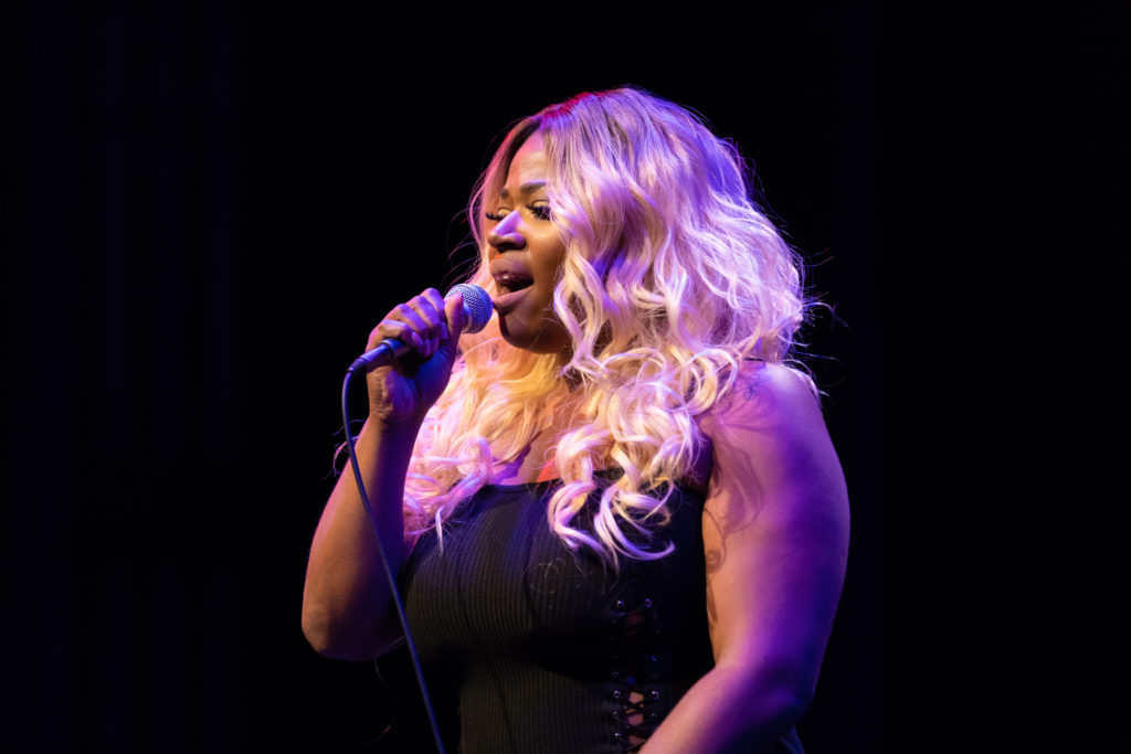 A black woman singer with long, blonde hair holds a mic while singing with the Band Bazaar.