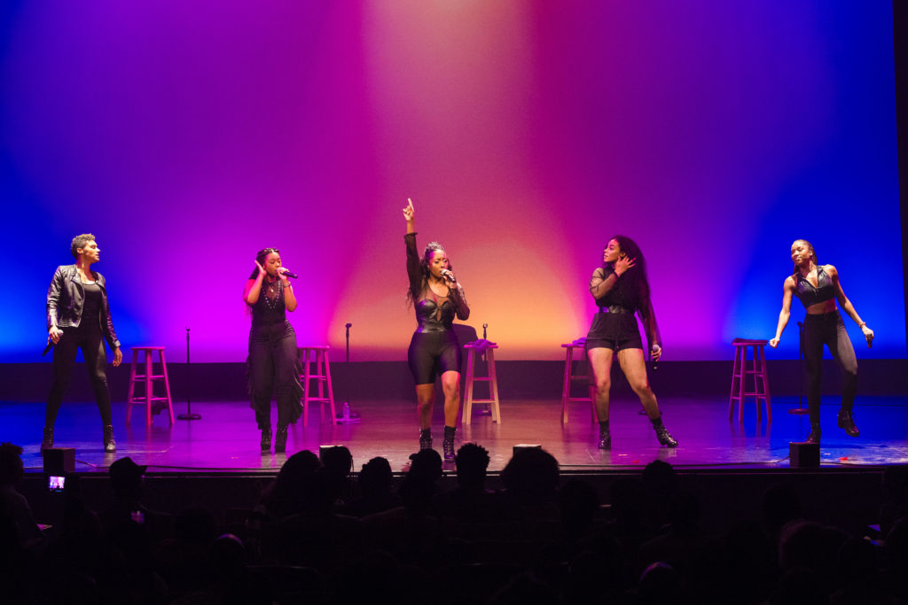 The five members of June's Diary sing and dance on stage.