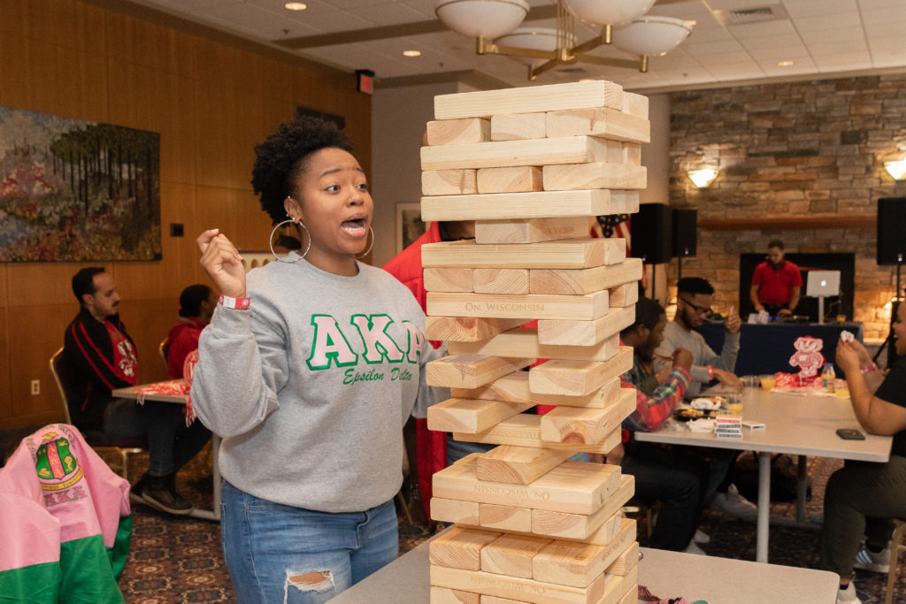 A woman wearing an Alpha Kappa Alpha sweatshirt has a surprised look on her face while playing Jenga.
