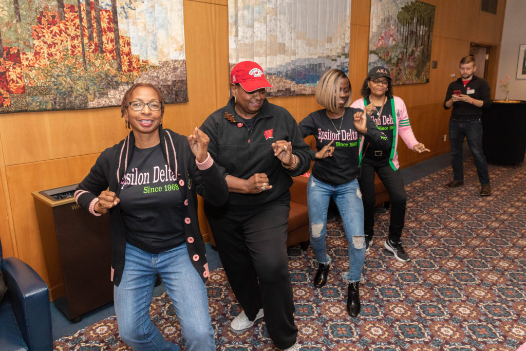 Four alumni members of the Alpha Kappa Alpha sorority perform a coordinated stroll routine around a room.