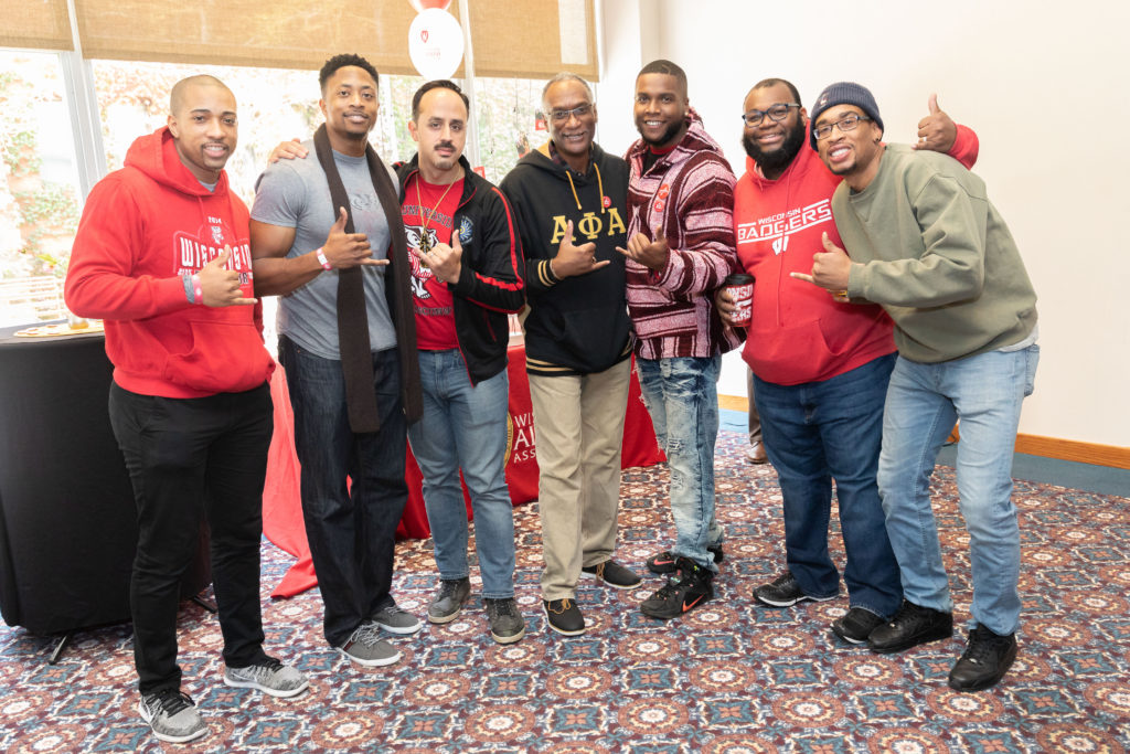 Seven alumni members of the Alpha Phi Alpha fraternity hold up a hand symbol of their frat while posing for the camera.