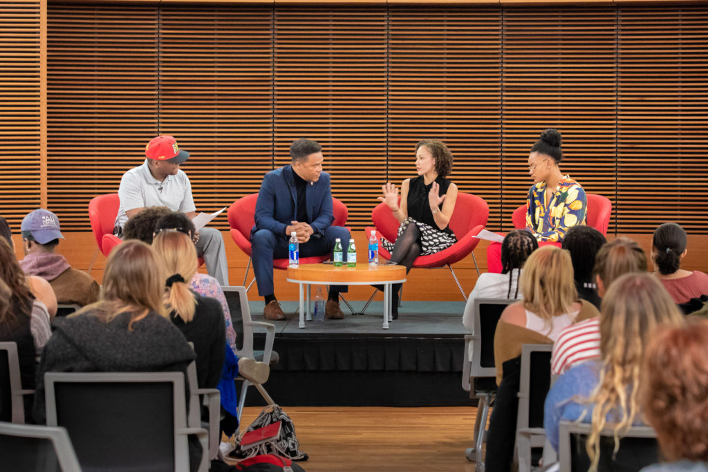 Four people are seated in red chairs in front of an audience at the RedTalk. The people are Anthony Ward, Frank Gatson Jr., Rebecca Arends and Nia Scott.