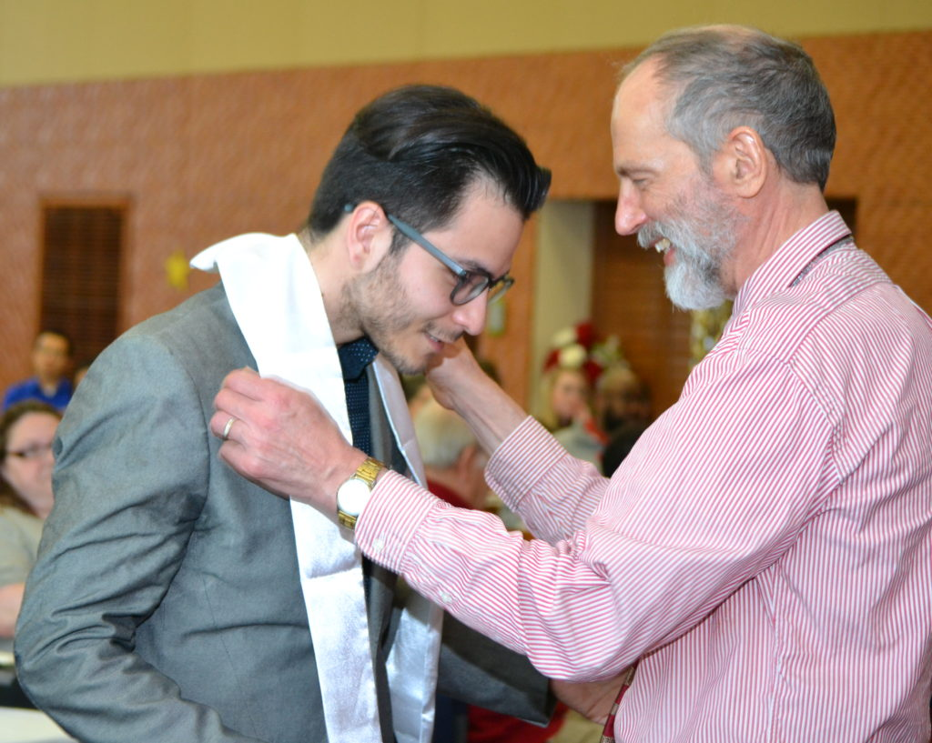 Kirk Malnor, right, puts on 2018 CeO graduate Jesus Del Toro's official stole.