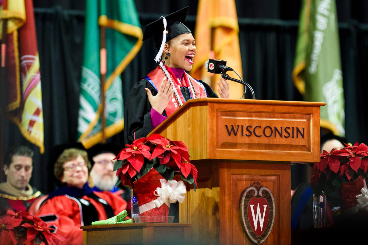 """Jamie Dawson stands at a podium bearing the word """"Wisconsin"""" and the UW crest and speaks into a microphone while wearing a traditional cap and gown with colorful stoles. Chancellor Becky Blank and others sit in the background watching her speech."""