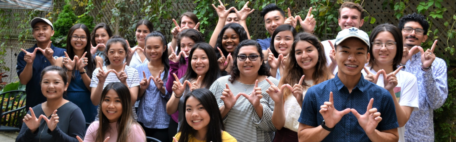 22 college student interns are grouped smiling and making W signs with their hands