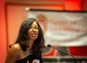 CeO Director Claudia Mosley speaks into a microphone at a podium with a banner in the background bearing the logo of the Center for Educational Opportunity.