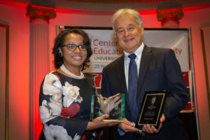 Cheryl Gittens and Walter Lane face the camera smiling while holding two award plaques on stage.