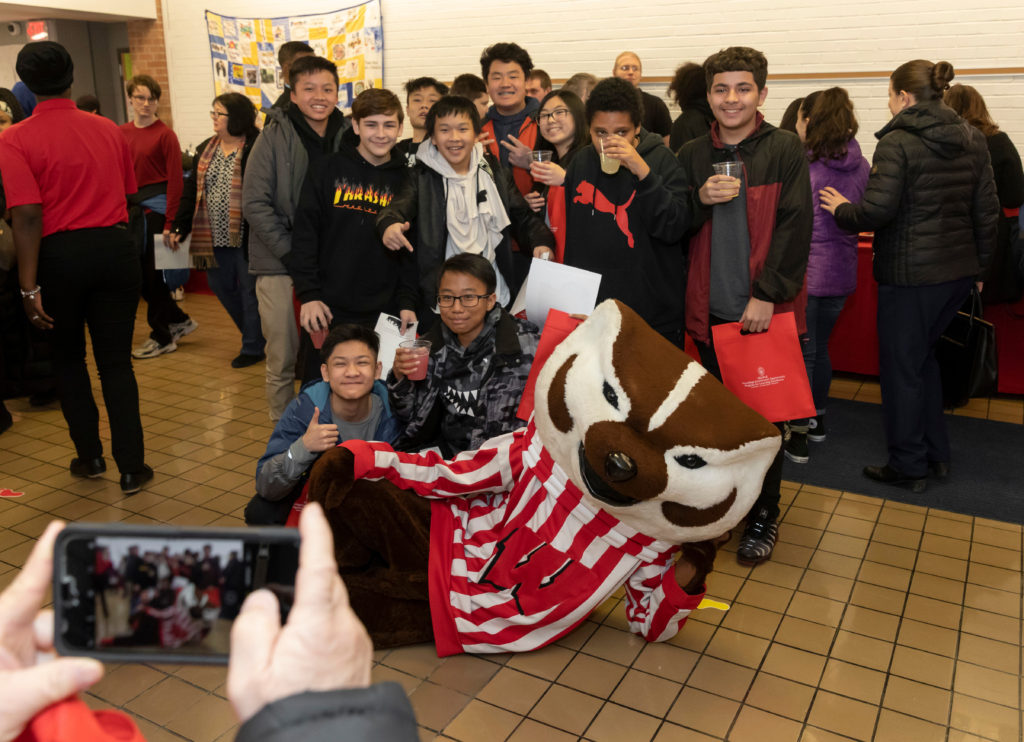 Students enjoy taking pictures with Bucky at the Grand opening of PEOPLE Program in Milwaukee Feb. 27, 2019. (Photo © Andy Manis)