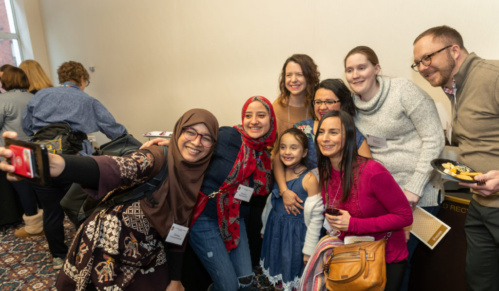 A group of women with a child and a man crowd together while one of them holds a phone out to take a selfie photo.