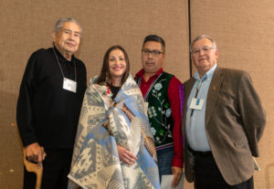 Melissa Metoxen stands with her grandfather and uncle and one more man. Melissa is draped in a blanket with Native designs and is holding a white eagle feather.