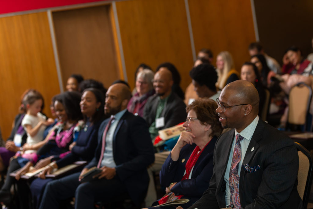 People in the audience smile as they watch a speaker. In the audience are Lt. Gov. Mandela Barnes, Chancellor Becky Blank and Deputy Vice Chancellor Patrick J. Sims.
