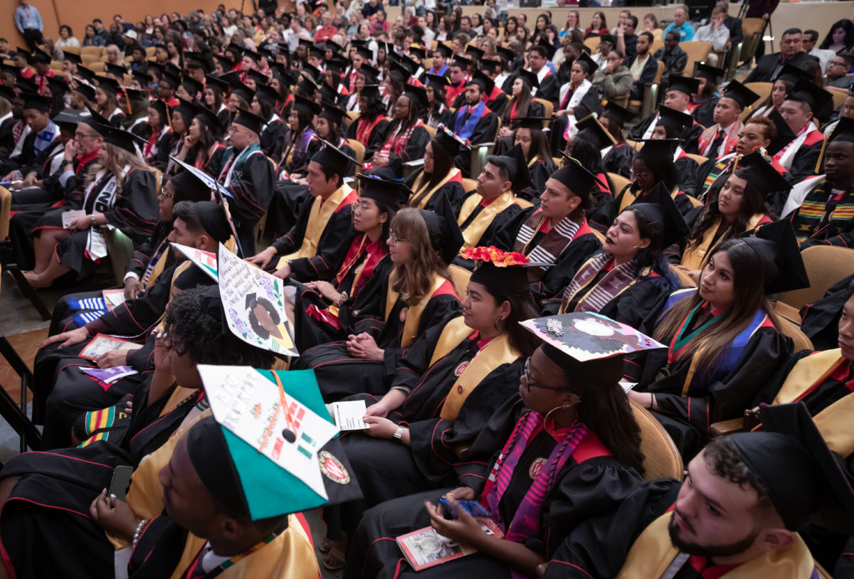 Graduating seniors in caps and gowns sit in auditorium seating in a large room.