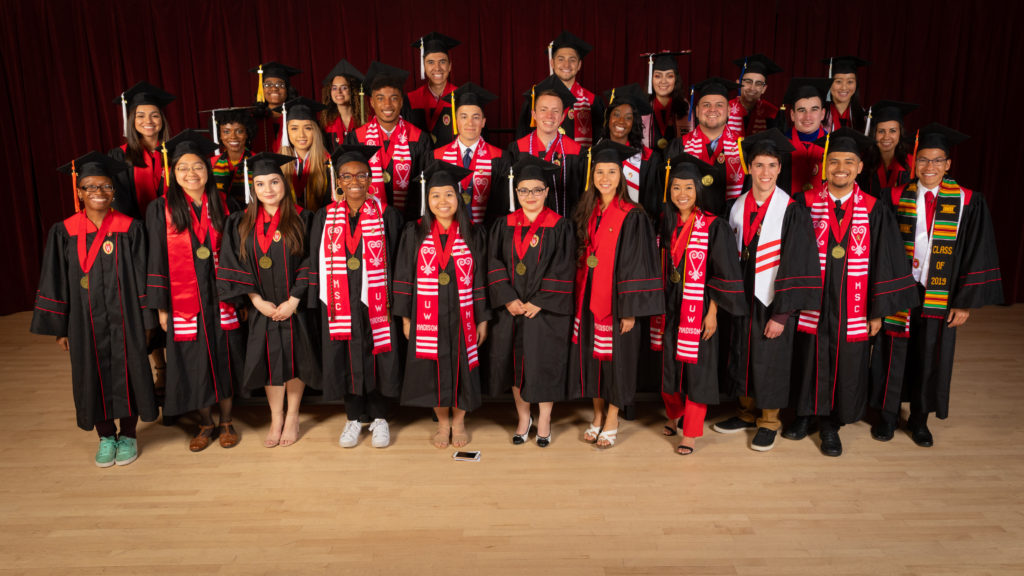 Twenty-eight graduating seniors from the Chancellor's Scholarship Program pose in their graduation robes and caps with round, gold medallions hanging around their necks.