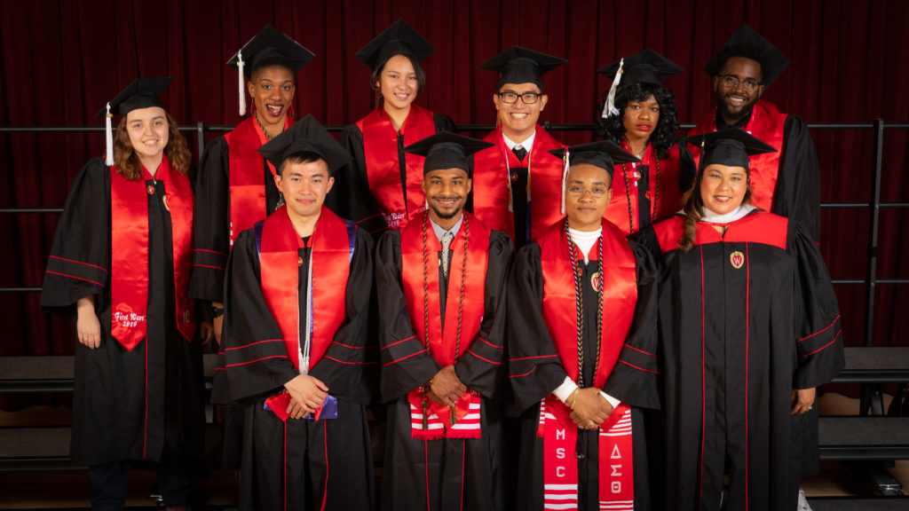 Nine graduating seniors and one staff member from the First Wave program pose in their graduation robes and caps with red stoles draped over their shoulders.