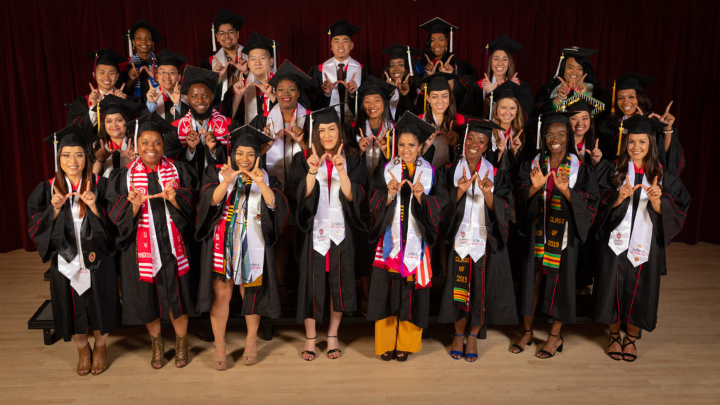 Twenty-six graduating seniors from the PEOPLE program pose in their graduation robes and caps with white stoles draped over their shoulders.