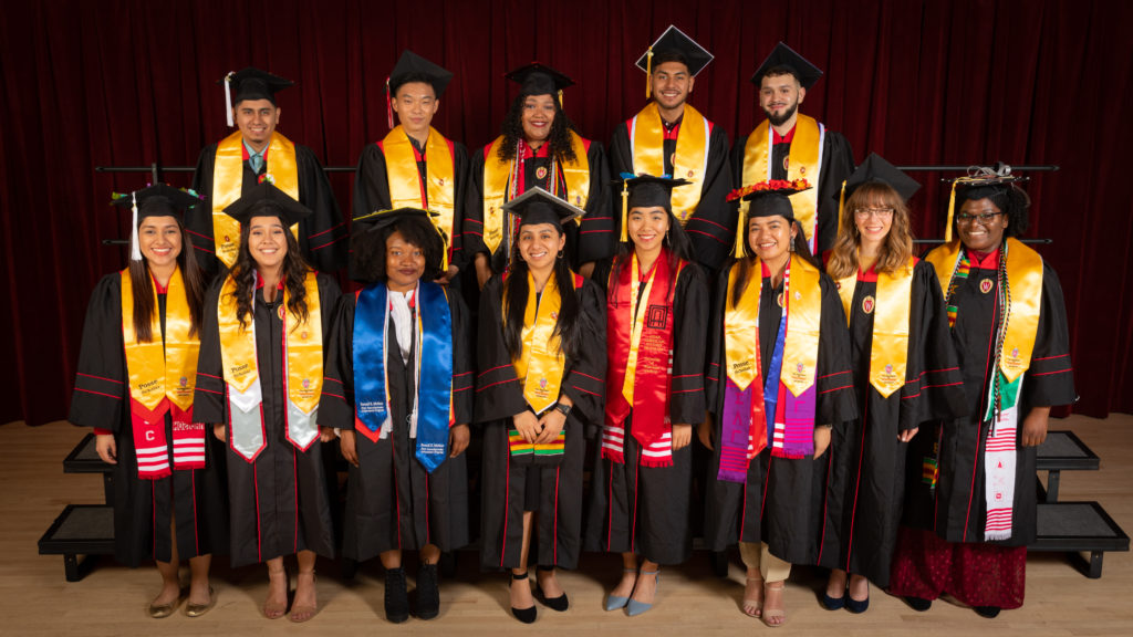 Thirteen graduating seniors from the Posse program pose in their graduation robes and caps with yellow stoles draped over their shoulders.