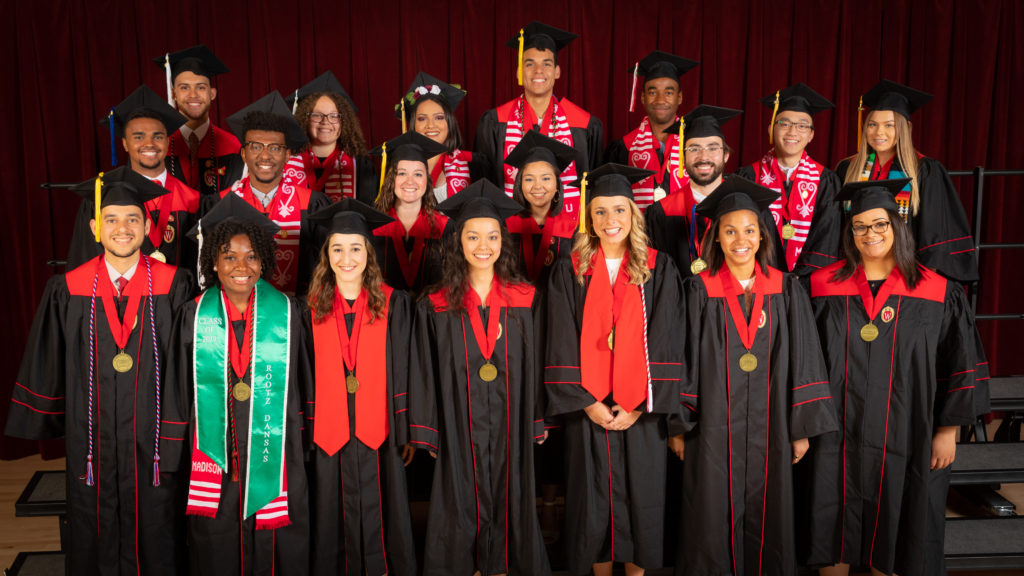 Nineteen graduating seniors from the Powers-Knapp Scholars program pose in their graduation robes and caps with round, gold medallions hanging around their necks