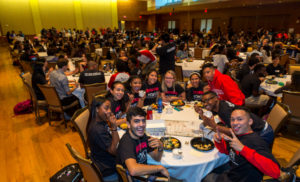 Hundreds of students sit at large, round tables in Union South Varsity Hall during Kickback. In the foreground, a group of students wearing PEOPLE program shirts smile and gesture while looking at the camera.