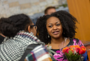 Bianca Baldridge holds a bouquet of roses while speaking with someone at the awards reception.