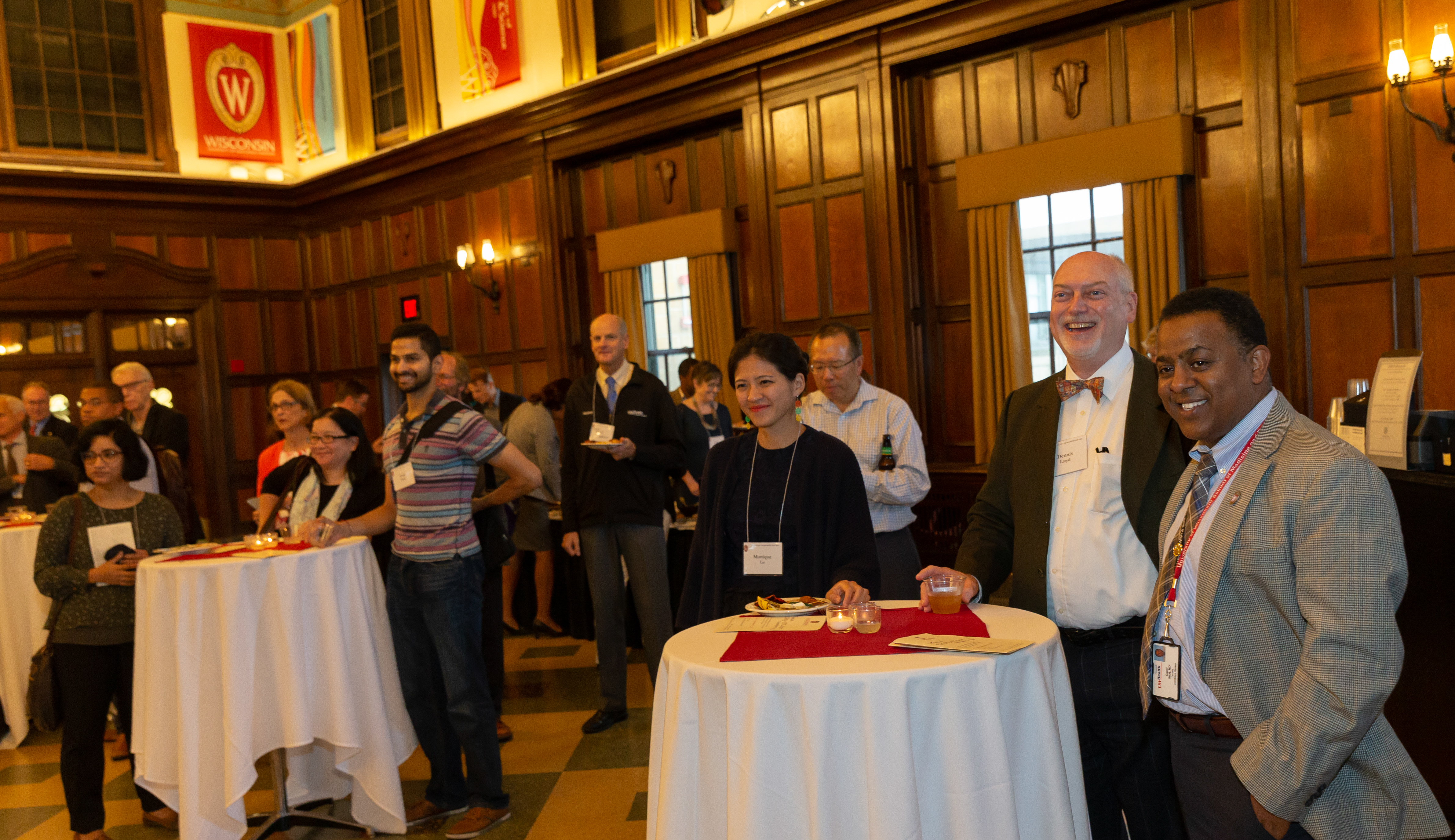 UW–Madison faculty members stand around small tables with drinks while watching a speaker who is not in the picture.