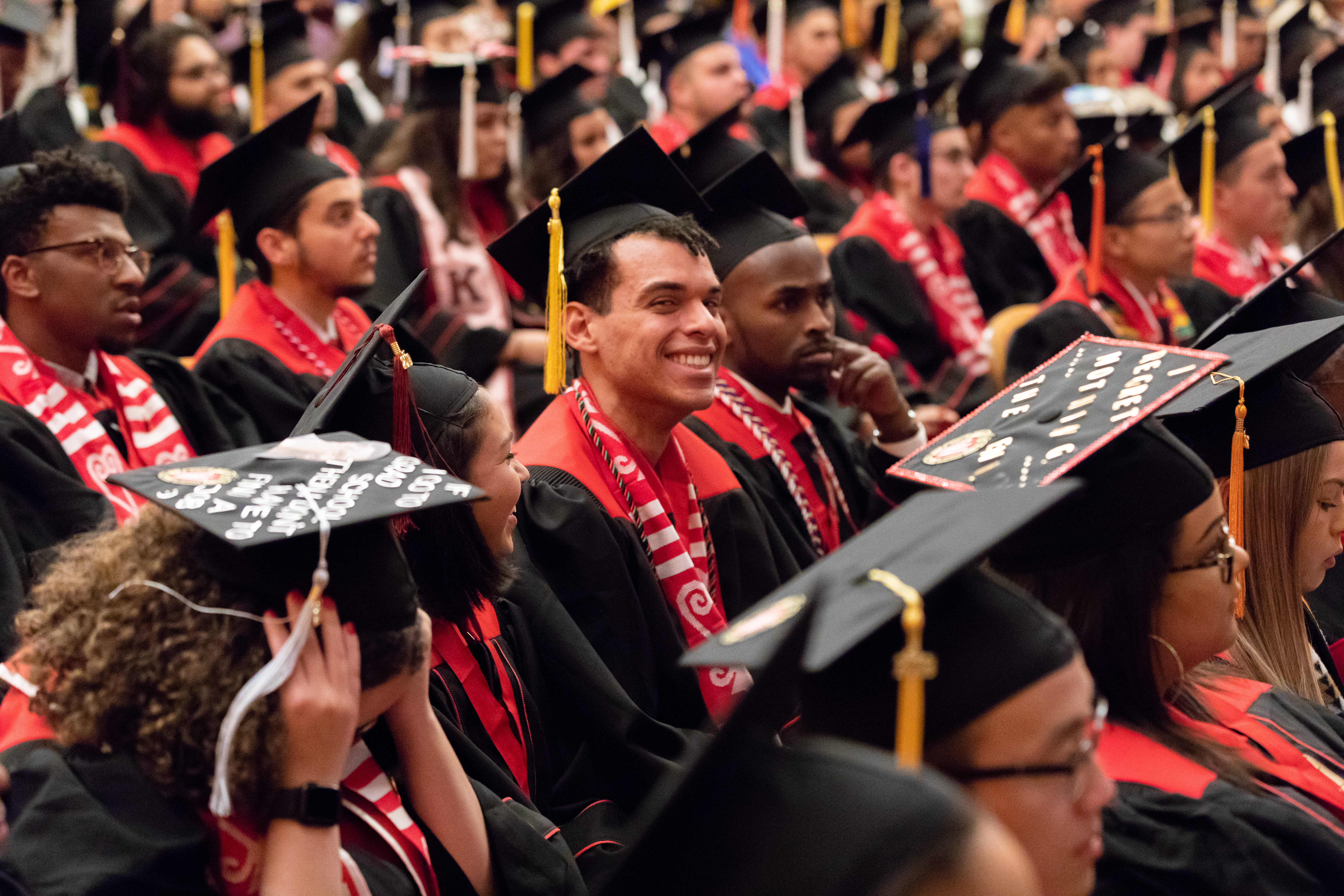 Graduating seniors in caps and gowns sit in a large hall facing the stage.