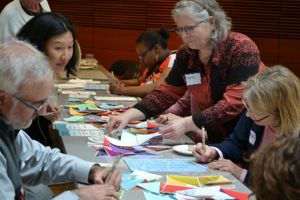 LI 20th Anniversary participants from Left Steve Shockler, Laura Klunder, Tanika Rumph, write congratulatory thoughts on cloth that will be assembled into a quilt by Nancy Blake (standing right). Far right, Marie Koko.