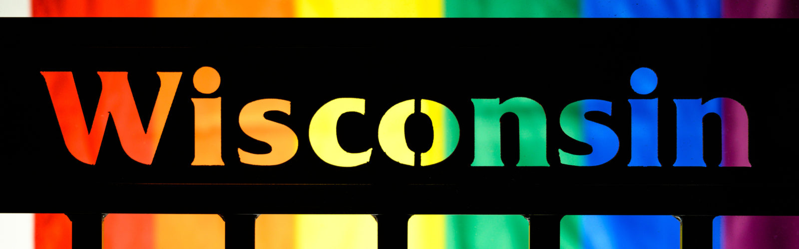 The word Wisconsin on the side of a bus shelter silhouetted against the rainbow colors of a Pride flag.