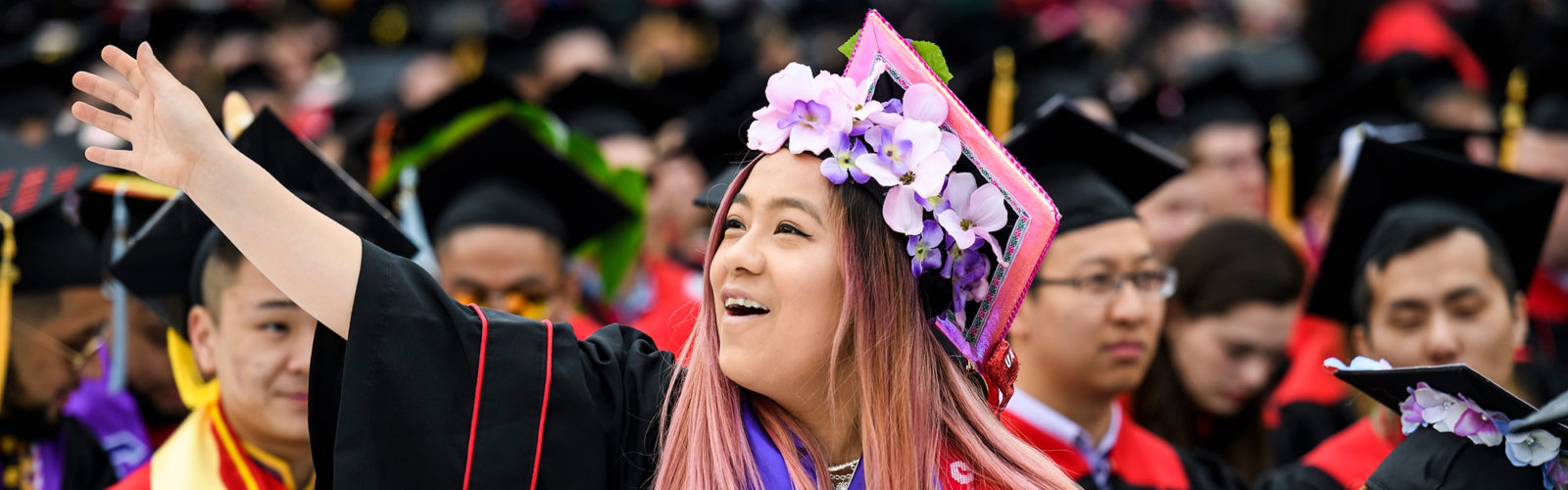 Photo of graduate Kimberly Vue waving to her family, wearing a pink mortarboard and a wreath of flowers.