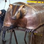 """A bronze statue, aptly named """"The Badger,"""" by late Ho-Chunk artist Harry Whitehorse, will be installed across the street from Camp Randall Stadium. Chris Andrews makes final touches on the casting at the Vanguard Sculpture Services workshop in Milwaukee. Photo by Deb Whitehorse,"""
