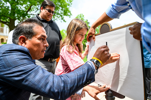 """Bird Bear helps Demetria Abangan-Brown Eagle create a crayon rubbing on paper from the """"Our Shared Future"""" plaque on Bascom Hill.PHOTO:BRYCE RICHTER"""