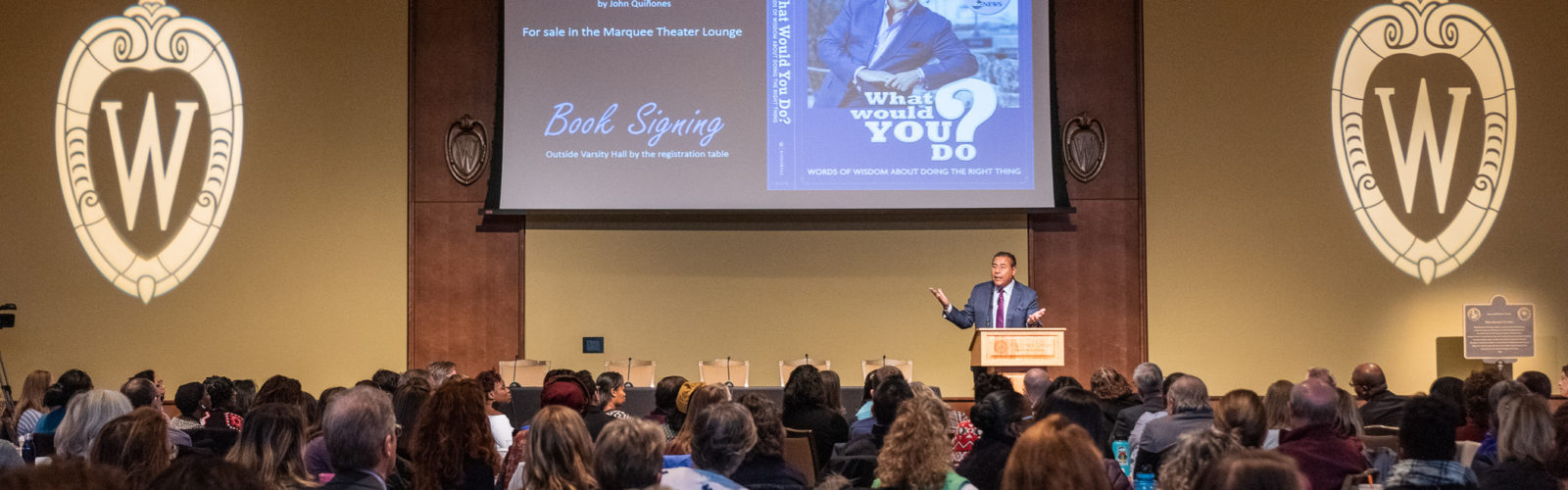 "John Quiñones gestures while speaking at a podium on a stage in front of a large, seated audience. A projection screen behind him shows a book cover with the title ""What Would You Do?"""