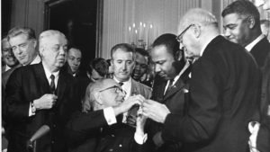 President Lyndon B. Johnson signs the 1965 Voting Rights Amendment with national leaders looking on and hands the ceremonial pen to the Rev. Dr. Martin Luther King, Jr. pe