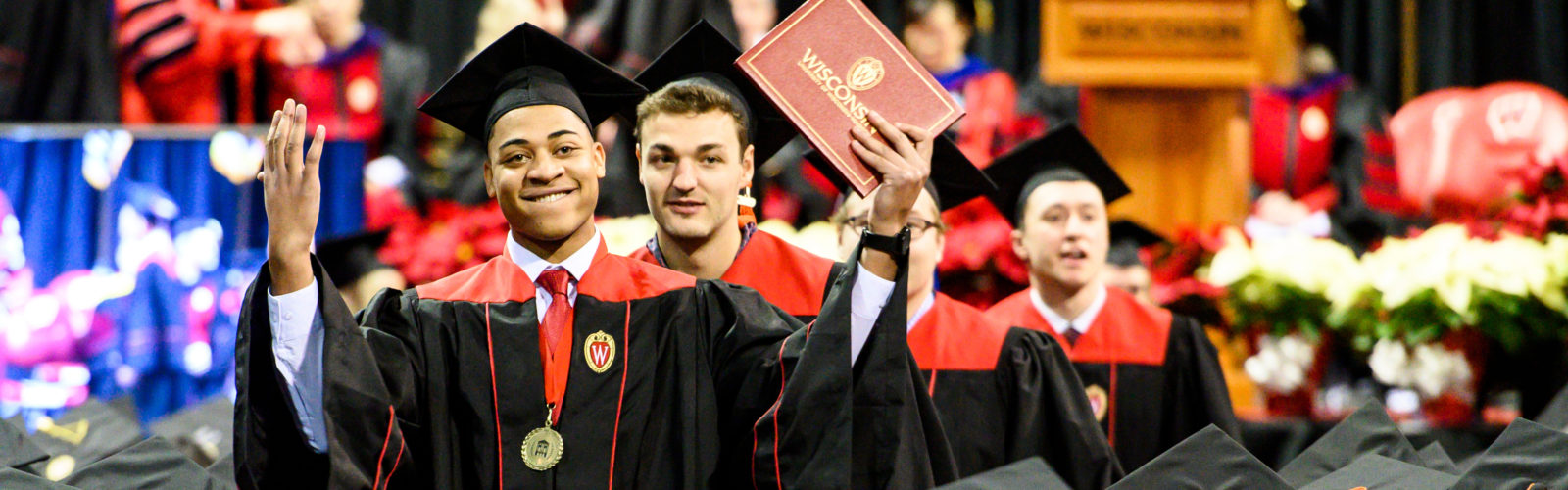 A man wearing a cap, gown and red hood makes a triumphant gesture while walking in line during the winter Commencement ceremony.