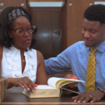 Manka and Everett Mitchell look in a large law book in a UW library.