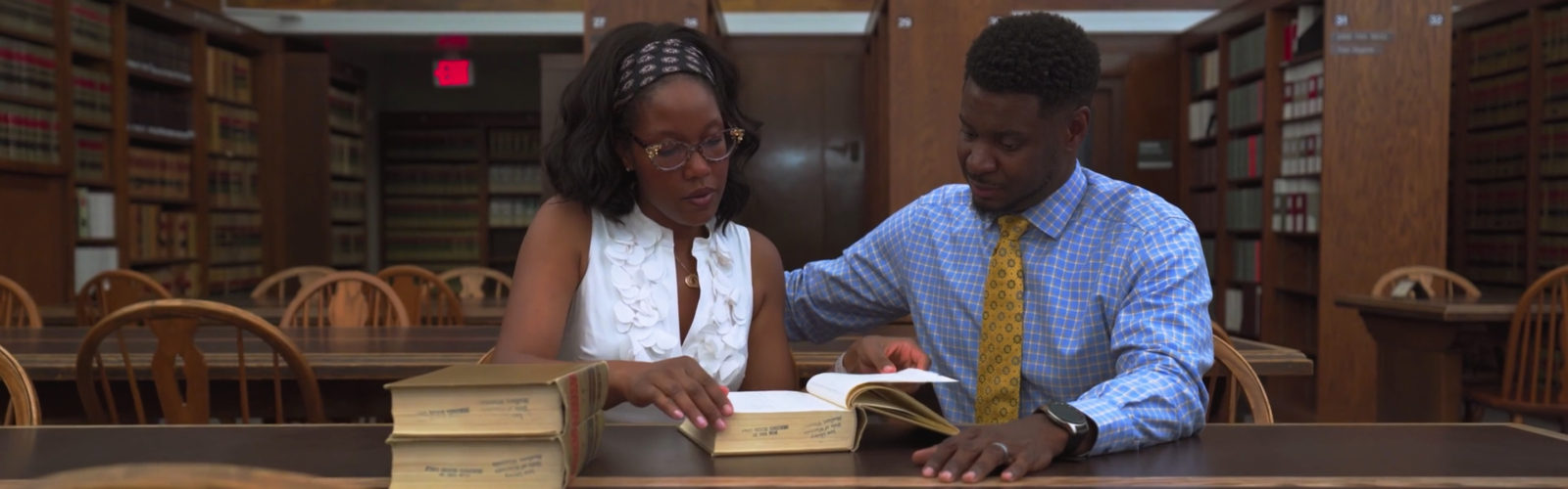 Manka and Everett Mitchell look at a law book together in a library.