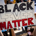 """Two hands hold up a sign reading """"BLACK LIVES MATTER"""" amidst a crowd of protesters."""