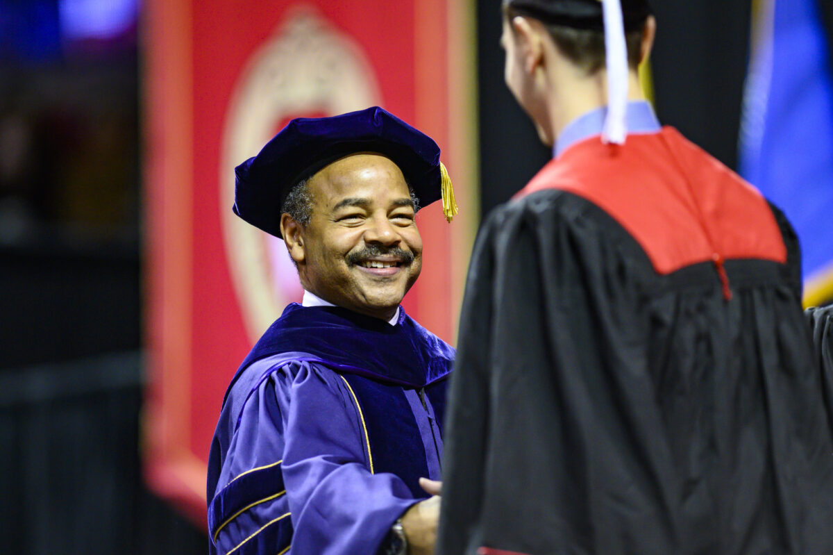 Eric Wilcots shakes a graduate's hand during the winter commencement ceremony held in the Kohl Center on Dec. 15, 2019. PHOTO: BRYCE RICHTER