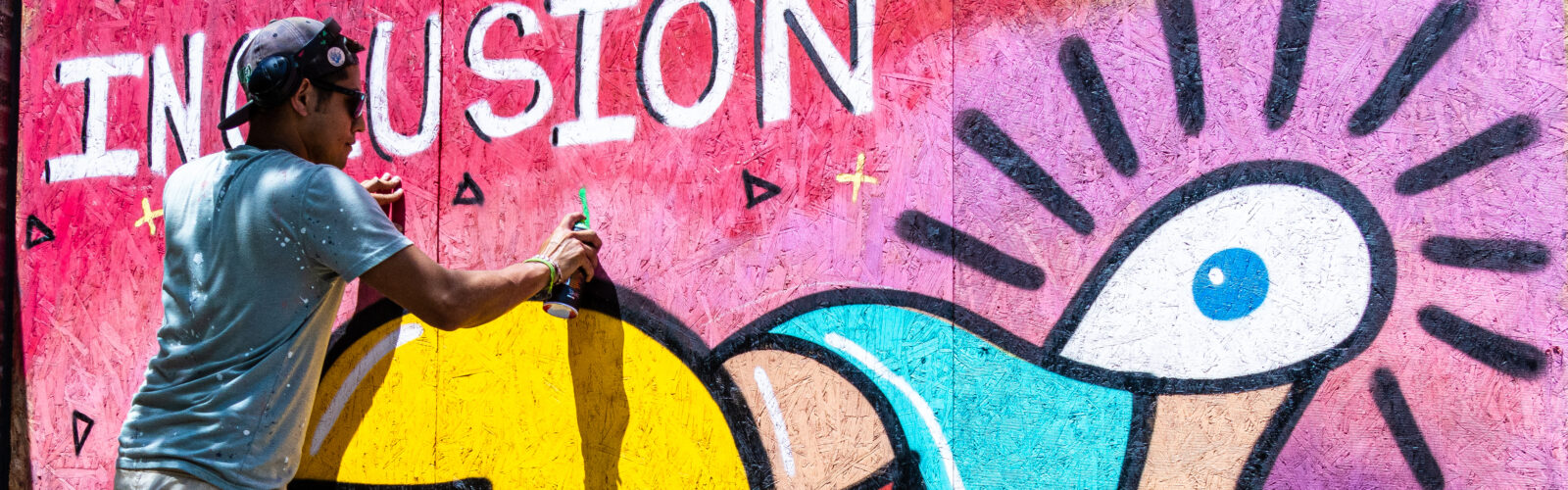 """A man stands on a ladder and sprays paint to create a large, colorful abstract image with the word """"INCLUSION"""" on plywood window coverings"""
