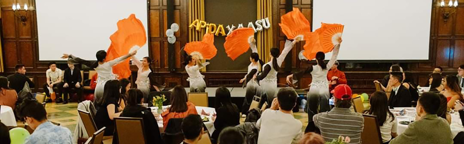 APIDA students watch dancers in white and black costumes performance with large orange fans perform