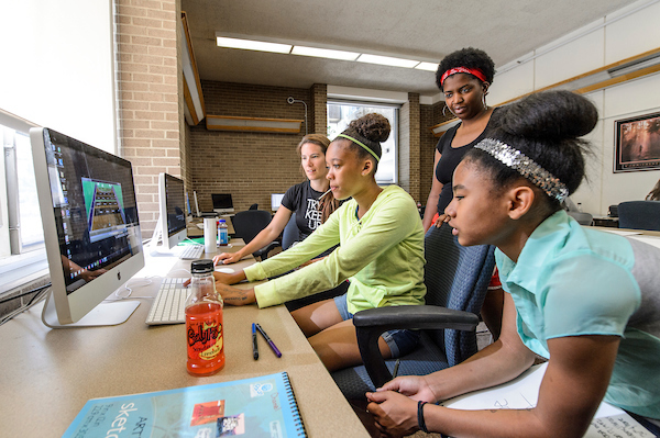 High school students Chane Skinner (center in green) and Micah Edwards-Sopha (far right) work with PEOPLE mentors Caitlin Iverson (left) and Shaya Glass (standing) to program video games during a Gaming for Girls Pre-College Enrichment Opportunity Program for Learning Excellence (PEOPLE) workshop in Witte Residence Hall at the University of Wisconsin-Madison on July 1, 2014. (Photo by Bryce Richter / UW-Madison)