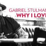 """Black and white image of a man with arm tattoos sitting at a table wearing a broad-rimmed hat with red lettering overlaid saying """"Gabriel Stulman - Why I Love UW"""""""
