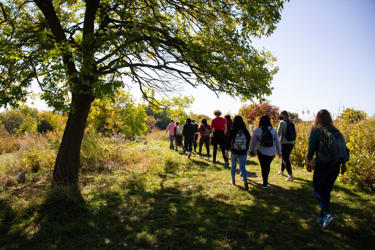 """Instructor Dan Cornelius leads students through the Biocore Prairie near Picnic Point during an agricultural workshop for the First-Year Interest Group """"Listening to Land: Indigenous Education, Language, and Foodways."""" PHOTO: CATHERINE REILAND/UW–MADISON"""