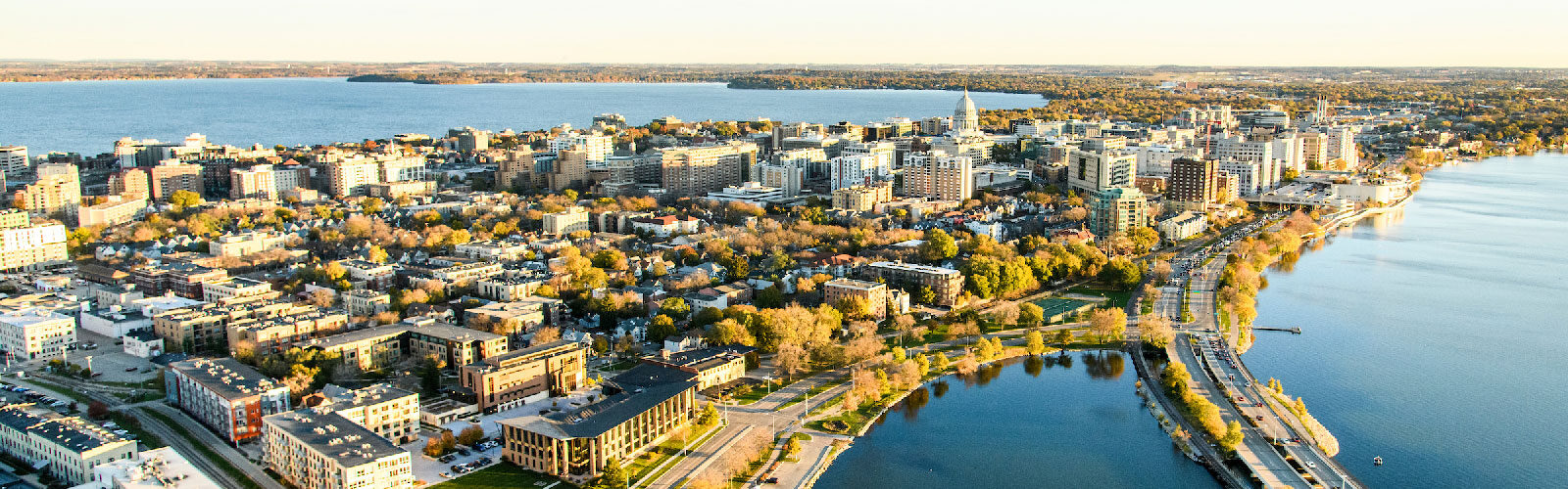 Aerial photograph of the isthmus of the city of Madison, showing lakes Mendota and Monona and the state Capitol building.