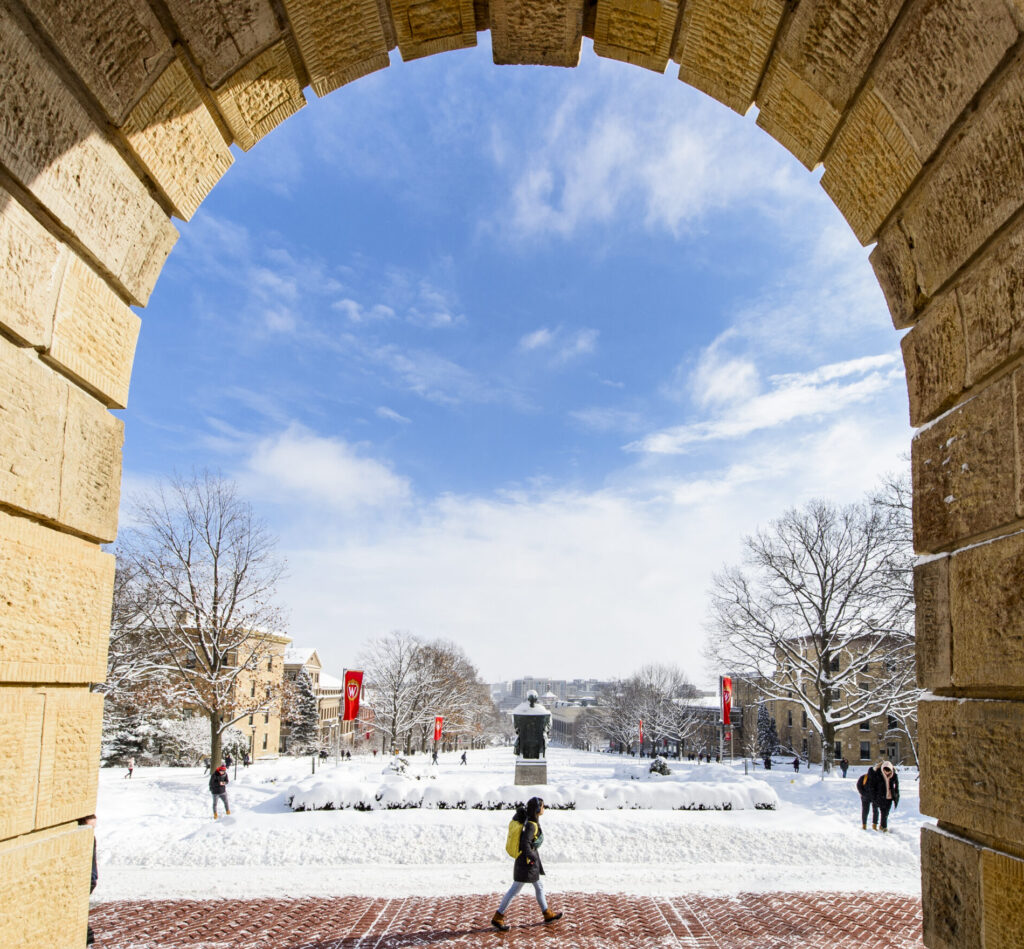 Photo from the front entrance of Bascom Hall looking out under a stone archway at a snowy Bascom Hill.