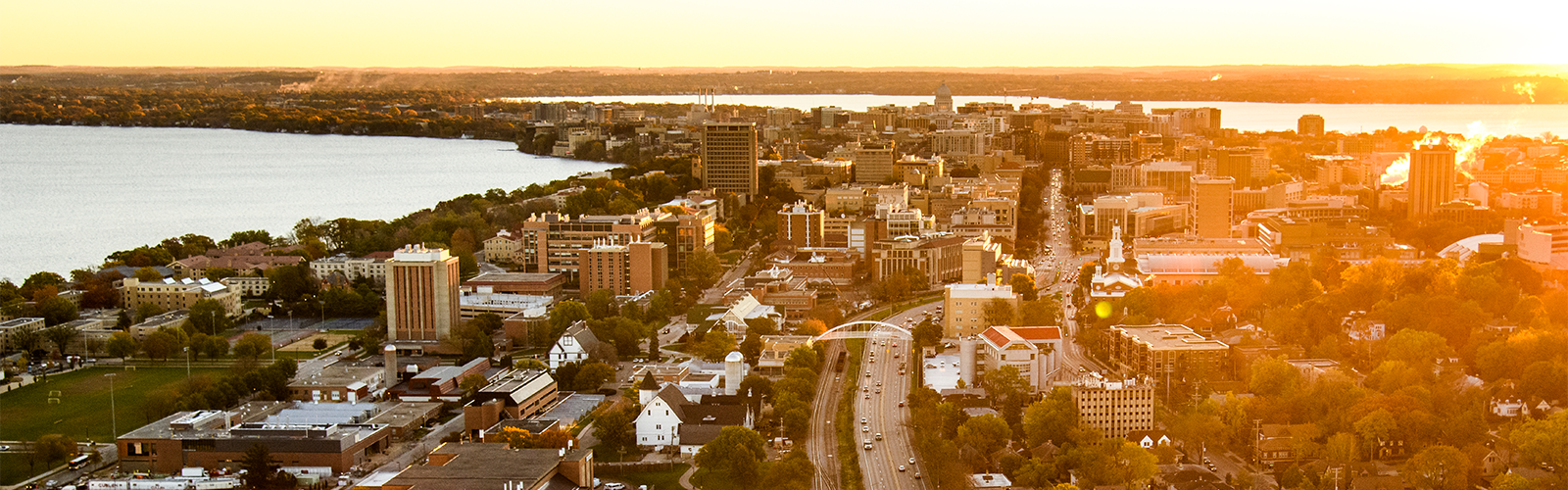 The UW–Madison campus on the Madison isthmus seen from an airplane with the sun rising on the horizon.