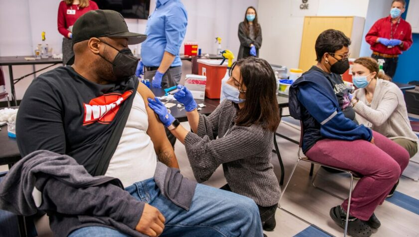 A vaccination clinic with masked people of color receiving vaccine shots from Pharmacy students.